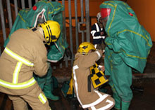 Firefighters in special airtight chemical protection suits dealing with ammonia leak during a training exercise