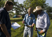 Howard Higgins, a FEMA community relations specialist and Louis Northrup, Oklahoma Emergency Management representative talk to a resident whose home was damaged in Shawnee