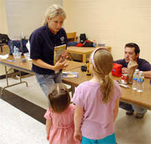 Public Affairs Specialist Neily Chapman shows children some of the items to pack in a disaster kit during a FEMA classroom presentation
