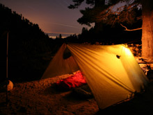 A tent lit up at night: fires in tents or caravans can spread very quickly