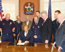 Maine firefighters, IAFF and government representatives sign the new state legislation providing compensatory benefits for firefighters who contract cancer