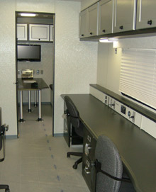 Mobile command interior with 4 workstations and conference/meeting room and kitchenette (not shown)