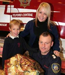 Manager Tony Druce with Sarah Gill and son Harrison Wheeler who won a hamper and a visit to Telford fire station