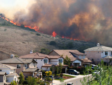 Fire encroaching on a residential street: to stay or defend property is a difficult decision for those living in wildfire-prone areas