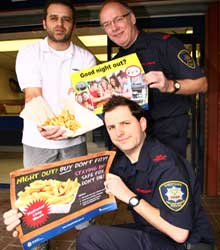 left to right…chip shop owner Simon Savva with fire risk reduction officers Andy Cooper and Shane Gazey (kneeling)