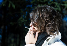 A woman smoking outside: according to a new study, more and more people are reacting to the ban on smoking in public buildings by smoking outside their homes, too