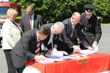 Signing the contract from left: Liz Barron; Roger Startin; Ian Mitchell (signing); Terry Brewer; Chris Jones; Noel Roberts