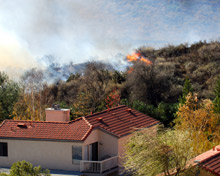 Wildfire approaching homes: damage to homes and businesses from wildfire is increasing throughout the US, as development puts more buildings in areas susceptible to fire