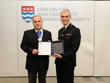 London Fire Commissioner Ron Dobson receiving a fire mark for his 30 years service