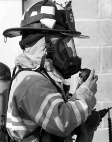 A firefighter adjusting the facepiece on her SCBA. USFA and NIST have begun a research study to examine how enhancements to SCBA facepieces can increase their protectiveness