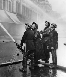 Members of the UK's Auxiliary Fire Service (AFS) fighting a fire on Oxford Street during World War II. The London Fire Brigade is holding a national event to celebrate the anniversary of the AFS