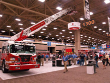 Crimson Fire's booth at Fire Rescue International includes displays of its Legend and Star series pumpers, a First Response All Call concept vehicle, and a custom mid-mount aerial platform